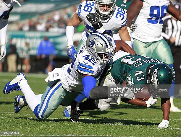 Darren Sproles of the Philadelphia Eagles runs 11 yards for a first down and is tackled by Barry Church of the Dallas Cowboys during the first...