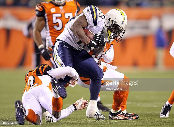 Darren Sproles of the San Diego Chargers runs with the ball while tackled by Johnathan Joseph and Keiwan Ratliff of the Cincinnati Bengals in the NFL...