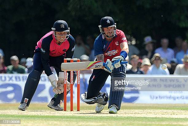 Darren Stevens of Kent lines up a sweep while Adam Rossington of Middlesex looks on during the Friends Life T20 match between Middlesex Panthers and...