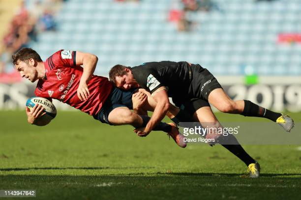 Darren Sweetnam of Munster Rugby is tackled by Alex Goode of Saracens during the Champions Cup Semi Final match between Saracens and Munster at Ricoh...