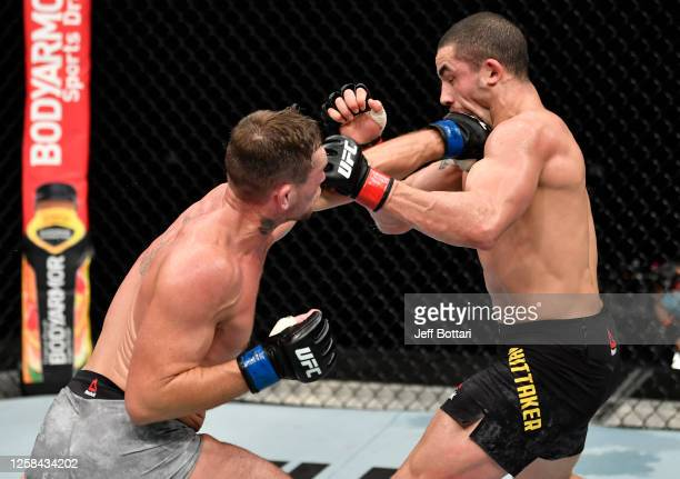 Darren Till of England punches Robert Whittaker of New Zealand in their middleweight fight during the UFC Fight Night event inside Flash Forum on UFC...