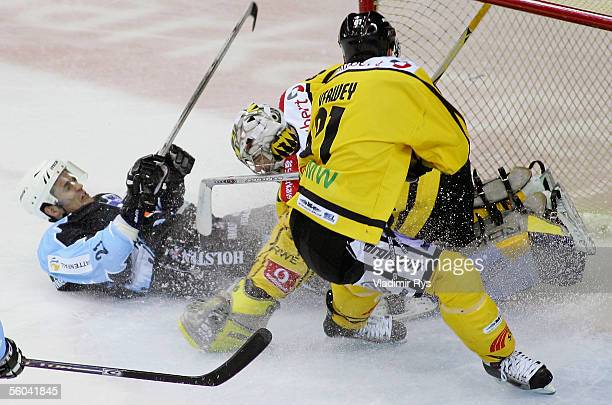 Darren Van Impe of Hamburg clashes with goalkeeper Robert Muller of Krefeld as his team mate Roland Verwey tries to stop the puck before the goal...