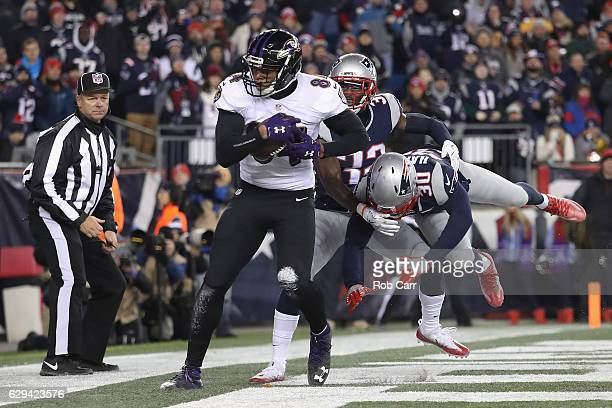 Darren Waller of the Baltimore Ravens makes a touchdown reception as he is defended by Duron Harmon and Devin McCourty of the New England Patriots...