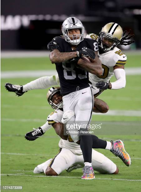 Darren Waller of the Las Vegas Raiders catches the ball while being defended by P.J. Williams and Janoris Jenkins of the New Orleans Saints at...