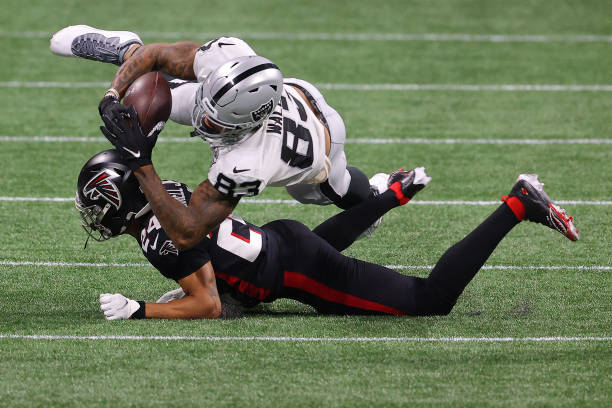Darren Waller of the Las Vegas Raiders is tackled by A.J. Terrell of the Atlanta Falcons during their NFL game at Mercedes-Benz Stadium on November...