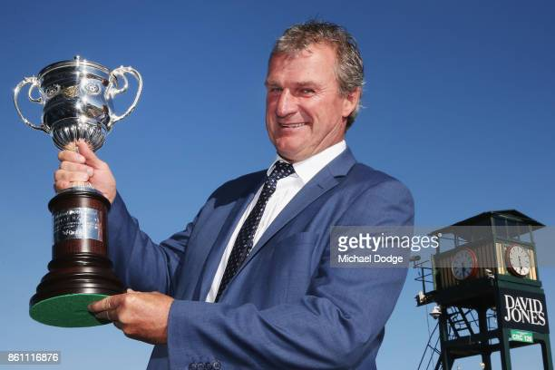 Darren Weir trainer of Tosen Stardom holds up the trophy after winning race 9 the United Petroleum Toorak Handicap during Melbourne Racing on...