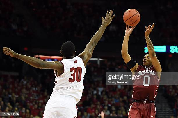 Darrion StrongMoore of the Oklahoma Sooners shoots over Vitto Brown of the Wisconsin Badgers during the second half of a game at the Kohl Center on...