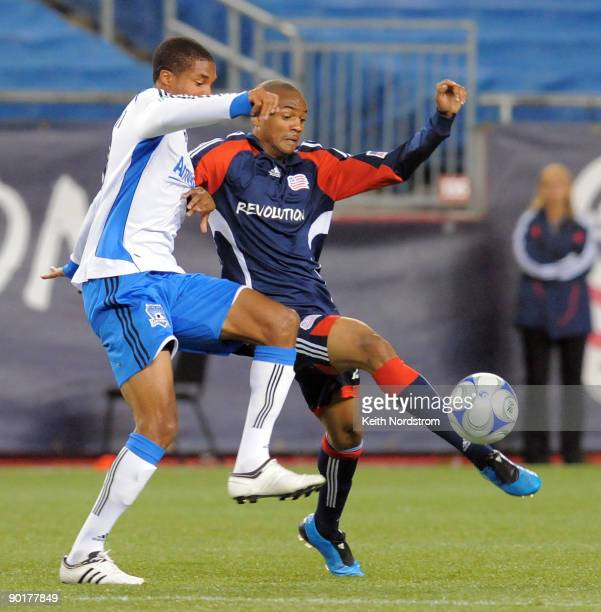 Darrius Barnes of the New England Revolution kicks the ball away from Ryan Johnson of the San Jose Earthquakes during MLS match August 29 at Gillette...