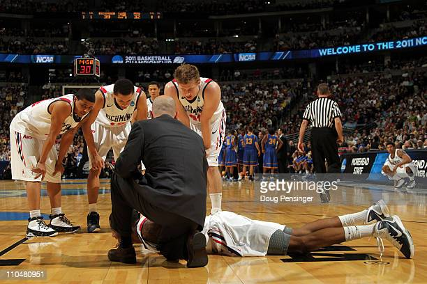 Darrius Garrett of the Richmond Spiders lis tended to after gettting injured on a play as teammates Kevin Anderson Kevin Smith and Dan Geriot look on...