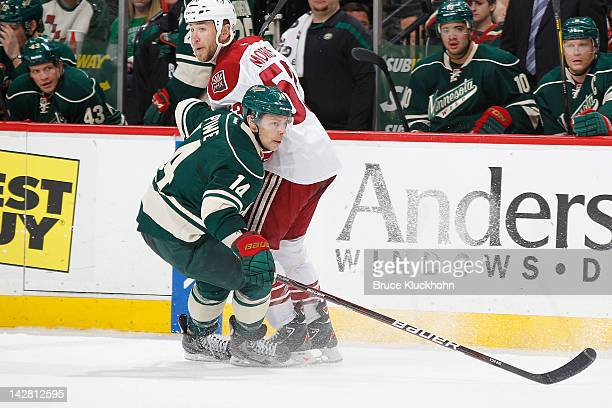 Darroll Powe of the Minnesota Wild and Derek Morris of the Phoenix Coyotes skate to the puck during the game at the Xcel Energy Center on April 7...