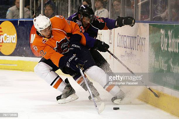 Darroll Powe of the Philadelphia Phantoms and Kyle Okposo of the Bridgeport Sound Tigers play for possession of the puck during the third period on...