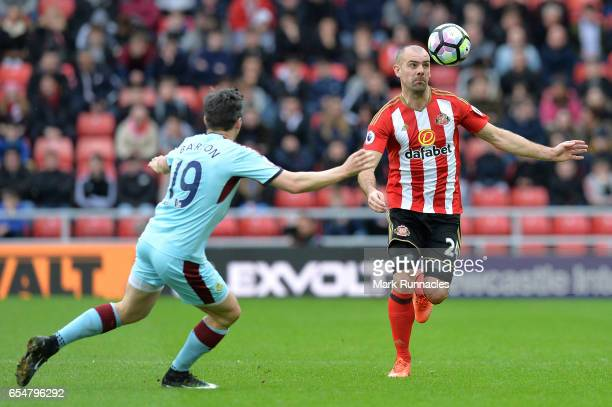 Darron Gibson of Sunderland controls the ball while under pressure from Joey Barton of Burnley during the Premier League match between Sunderland and...