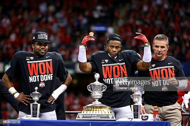 Darron Lee and Ezekiel Elliott and head coach Urban Meyer of the Ohio State Buckeyes celebrate with the trophy after defeating the Alabama Crimson...