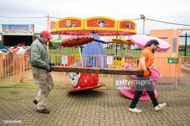 Darron McCleave and Garry Culling carry painted posts through the site as they continue to prepare the Leisure Island fun park for the approaching...