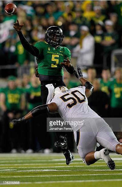 Darron Thomas of the Oregon Ducks is forced throws an interception as he is pressured by Aaron Tipoti of the California Golden Bears on October 6...