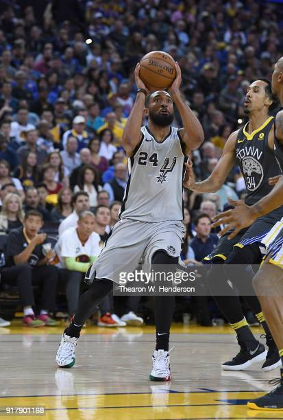 Darrun Hilliard of the San Antonio Spurs goes up to shoot over Shaun Livingston and David West of the Golden State Warriors during an NBA basketball...
