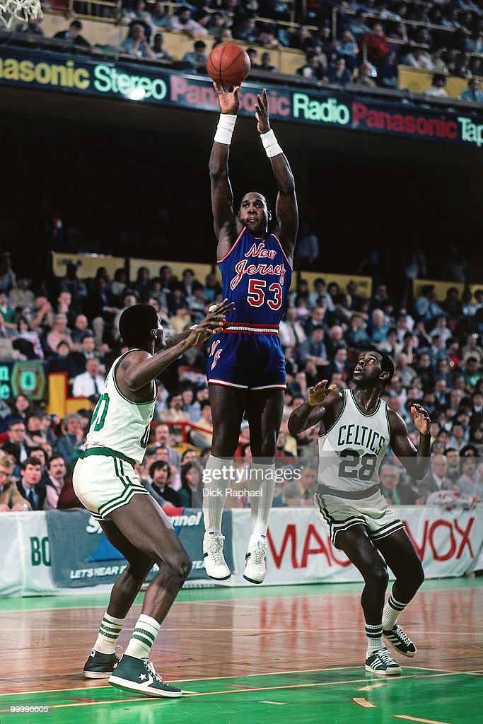Darryl Dawkins #53 of the New Jersey Nets shoots a jump shot against Robert Parish #00 and Quinn Buckner #28 of the Boston Celtics during a game played in 1983 at the Boston Garden in Boston, Massachusetts.