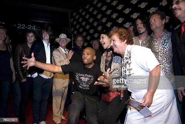 """Darryl """"DMC"""" McDaniels poses with celebrities including Rita Gilligan, cultural attache, dressed as a waitress, outside the newest Hard Rock Cafe at..."""