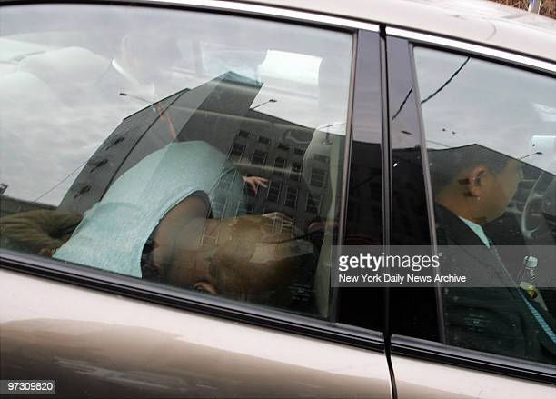 Darryl Littlejohn ducks his head in the back of a car as he is driven from Queens Supreme Court to the 112th Precinct stationhouse for a lineup...