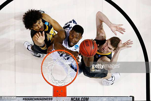 Darryl Reynolds of the Villanova Wildcats attempts to rebound against Dom Uhl and Adam Woodbury of the Iowa Hawkeyes in the first half during the...
