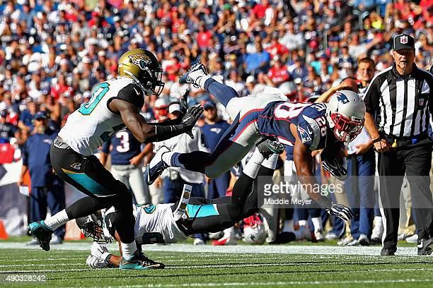 Darryl Roberts of the New England Patriots dives over Demetrius McCray of the Jacksonville Jaguars during the fourth quarter at Gillette Stadium on...