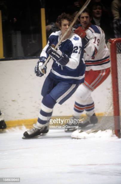 Darryl Sittler of the Toronto Maple Leafs skates around the net with Jean Ratelle of the New York Rangers defending circa 1972 at the Madison Square...