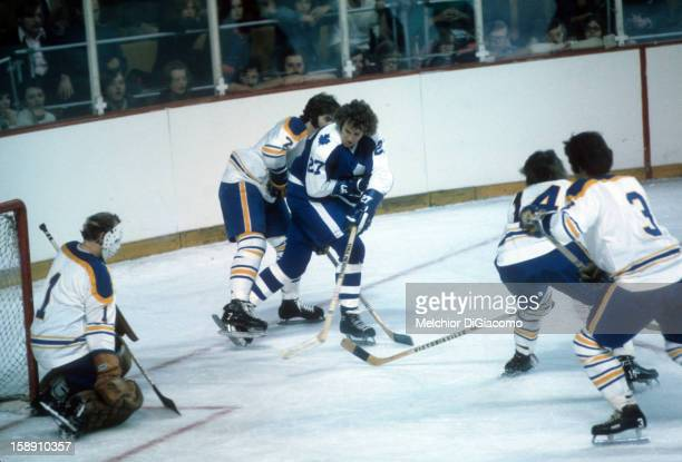 Darryl Sittler of the Toronto Maple Leafs tries to get a shot on goalie Roger Crozier of the Buffalo Sabres as Rick Martin of the Sabres defends...