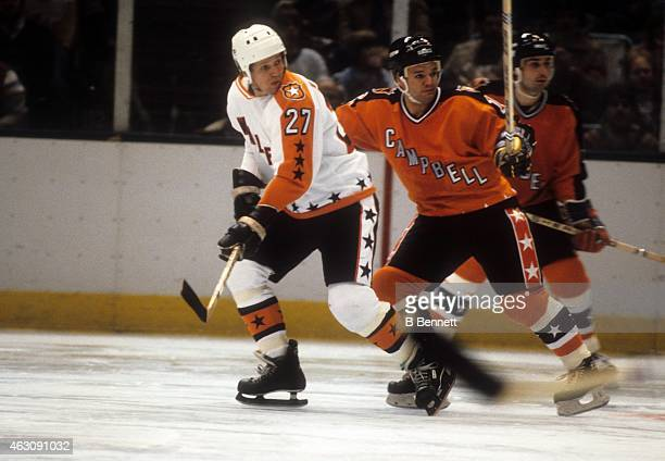 Darryl Sittler of the Wales Conference and the Philadelphia Flyers skates on the ice as he is defended by Marcel Dionne of the Campbell Conference...