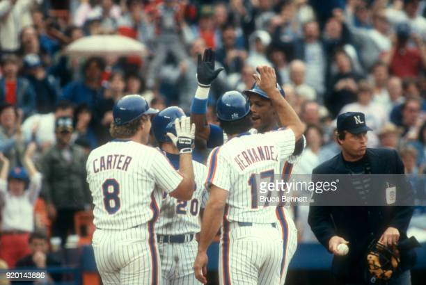 Darryl Strawberry of the New York Mets is congratulated by teammates Howard Johnson Gary Carter and Keith Hernandez after hitting a homerun during an...