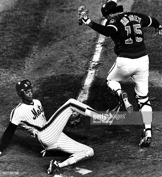Darryl Strawberry of the New York Mets slides into home as catcher Ron Hassey of the Chicago Cubs jumps out of the way during their game circa 1984...