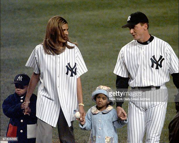 Darryl Strawberry's wife Charisse and two children are escorted to the mound by Yankees' pitcher David Cone to throw out the first ball before game...