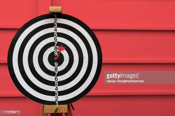 dart arrow hitting in the target center of dartboard - exatidão - fotografias e filmes do acervo