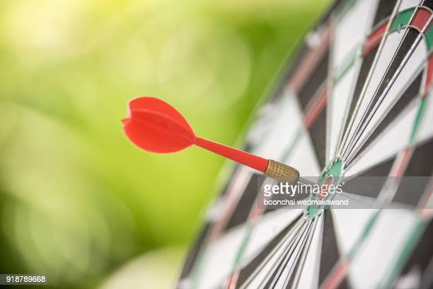 dart arrow hitting in the target center of dartboard - sports target stock pictures, royalty-free photos & images