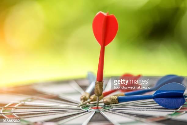 dart arrow hitting in the target center of dartboard - punkten stock-fotos und bilder