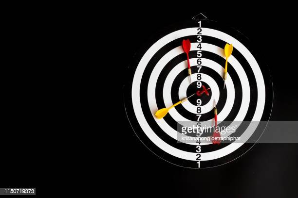 dart arrow hitting in the target center of dartboard,arrow on a black background - scoring stock pictures, royalty-free photos & images