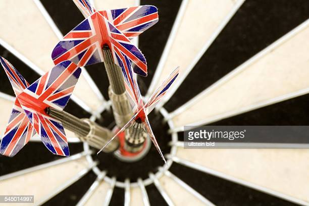 Dart arrows with Britsh national emblem sticking in the target of a dartboard