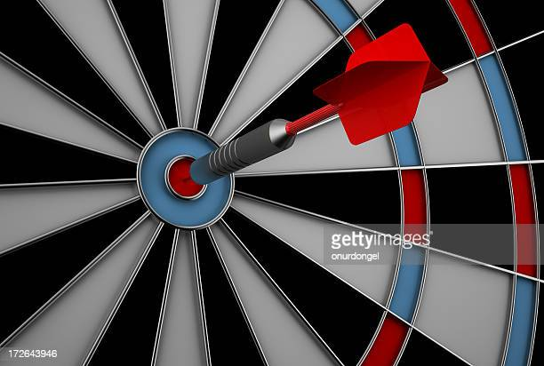 Dart hitting bullseye on dart board