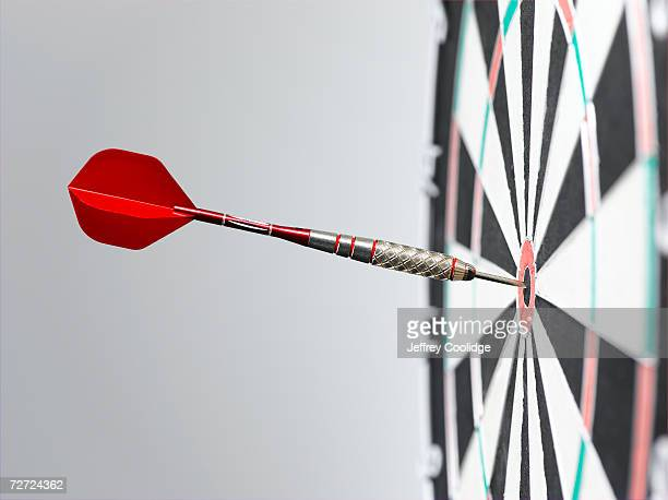 dart in bullseye of dart board, side view, close-up - dartboard stock pictures, royalty-free photos & images