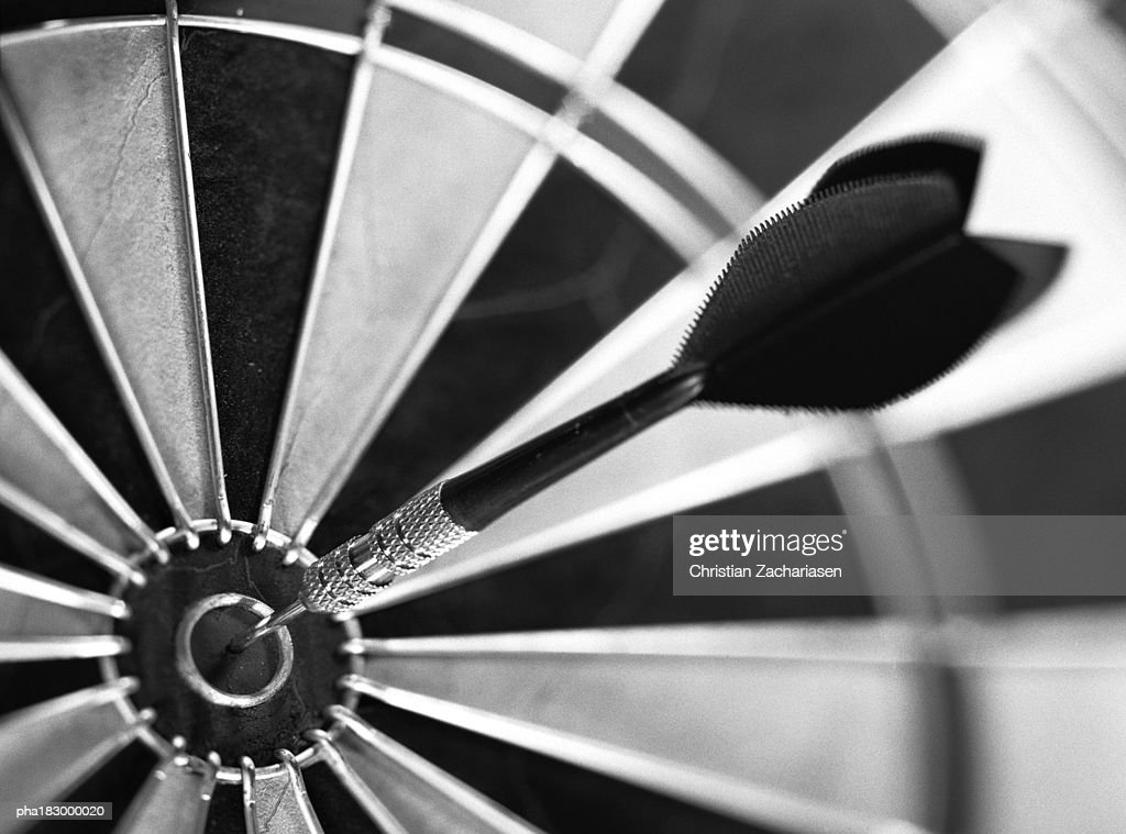 Dart in center of dartboard, close-up, b&w : Stock Photo