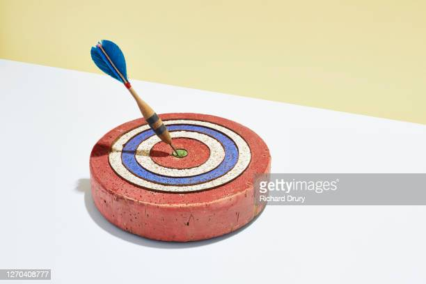 a dart in the bullseye of a dart board - richard drury stock pictures, royalty-free photos & images