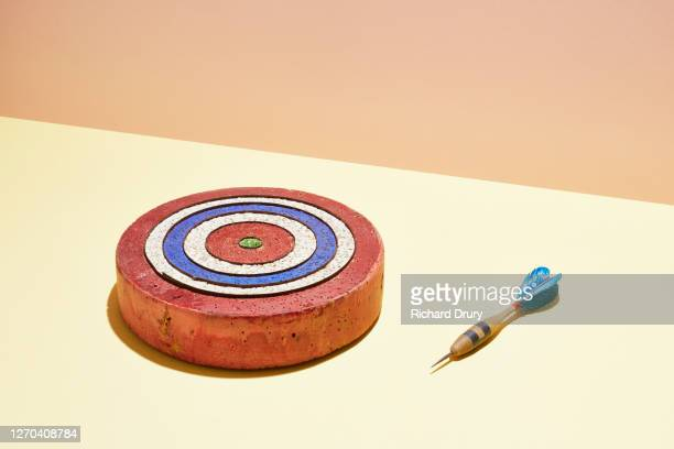 a dart lying next to a dart board - richard drury stock pictures, royalty-free photos & images