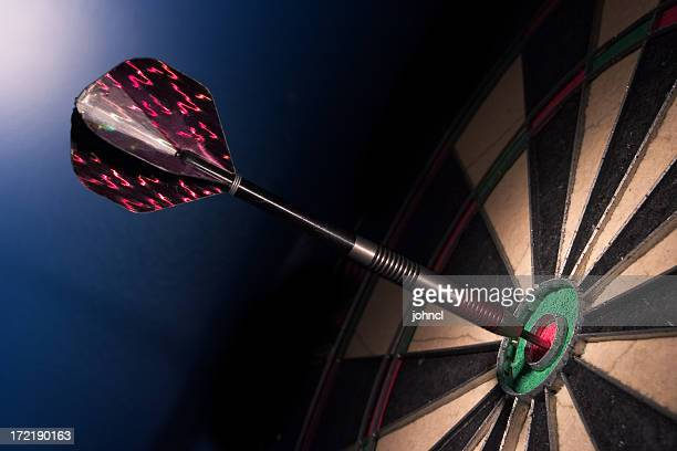 Dart resting in the bullseye of a dartboard, side shot