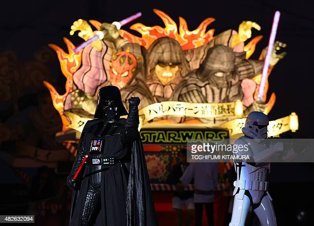 Darth Vader and storm trooper pose in front of the Star Wars Nebuta float featuring Darth Maul, Sheev Palpatine and Darth Vader during the eve of the...