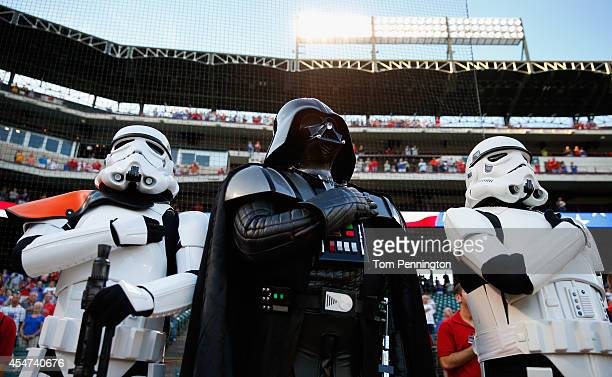 Darth Vader character from 501st Legion and two storm trooper characters stand during the National Anthem before the Seattle Mariners take on the...