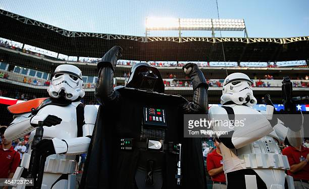 Darth Vader character from 501st Legion celebrates after throwing out the ceremonial first pitch as two storm trooper characters looks on before the...