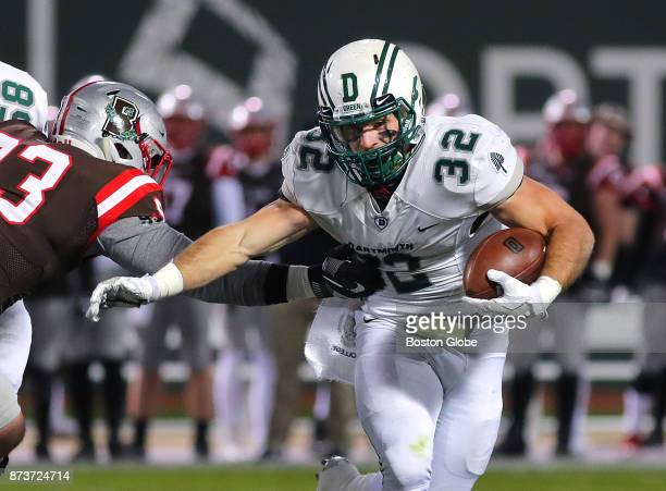 Dartmouth College's Ryder Stone carries the ball for a long first quarter gain as Brown's Michael Hoecht moves in for the tackle Dartmouth College...