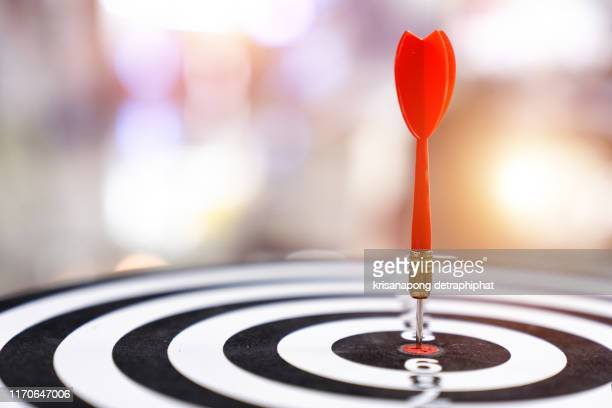 darts in center of the target dartboard on a light bokeh background. - business strategy stock pictures, royalty-free photos & images