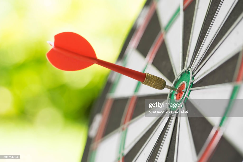 Darts in center of the target dartboard on a light green background : Stock-Foto