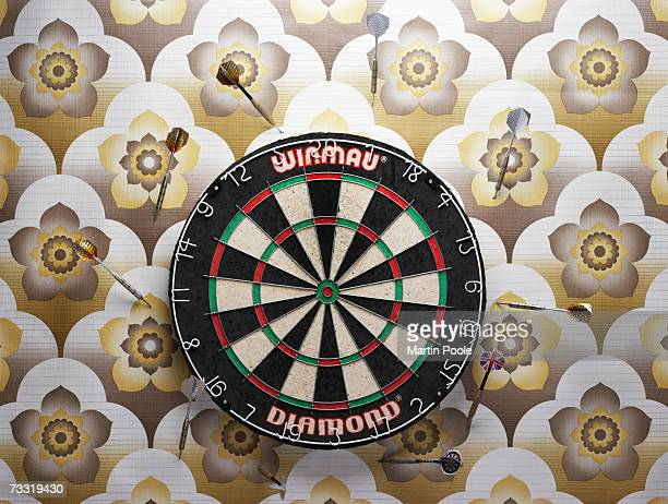 darts in wall around dart board - dartboard stock pictures, royalty-free photos & images