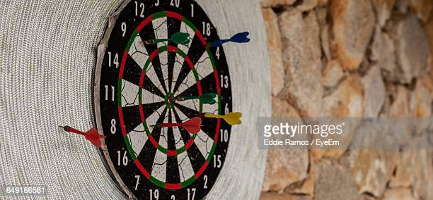 darts on sport target against stone wall at home - man cave stock pictures, royalty-free photos & images